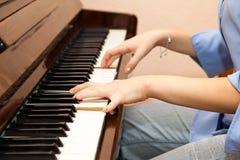 Hände eines jungen Mädchens, welches das Klavier spielt Lizenzfreies Stockfoto