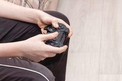 Hände eines kaukasischen Kindes, das einen schwarzen Konsolenauflagen-Prüfersteuerknüppel hält und Spiel spielt Obenliegende Ansi lizenzfreie stockbilder