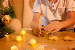 Hände eines Kindes, das Ingwerplätzchen in Form eines Herzens macht lizenzfreie stockfotos