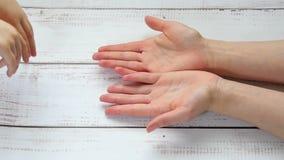 Hände eines Kindes im Mutter ` s übergibt Nahaufnahme, Hand in Hand vor dem hintergrund eines Holztischs, in der Zeitlupe stock footage