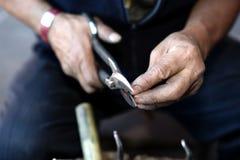 Hände eines Kupferschmieds Lizenzfreie Stockbilder