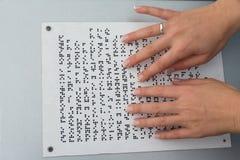 Hände eines Mädchens, das einen Text geschrieben auf Blindenschrift liest Stockbilder