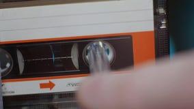 Hände eines Mannes, der eine kompakte Kassette rückspult stock video