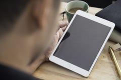 Hände eines Mannes, der leeres Tablettengerät über einer hölzernen Arbeitsplatztabelle hält Stockbilder