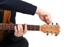 Hände eines Mannes in einem Schwarzen, das den Ton einer Gitarre abstimmt Getrennt auf weißem Hintergrund Lizenzfreie Stockfotos