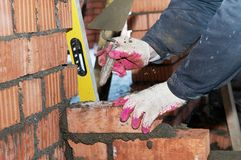 Hände eines Maurers an der Maurerarbeit Stockfotografie