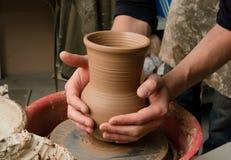 Hände eines Töpfers, ein tönernes Glas herstellend Stockfotos