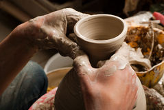 Hände eines Töpfers, ein tönernes Glas herstellend Lizenzfreie Stockfotos