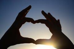 Hände in Form des Herzens gegen die Sonne und den Himmel eines Sonnenaufgangs oder des Sonnenuntergangs Liebe, Glück Lizenzfreies Stockfoto