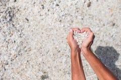 Hände in Form von Herzen mit Kieseln nach innen Lizenzfreie Stockfotos