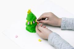Hände formen einen Pelzbaum vom Plasticine Stockfoto