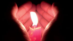 Hände formen wie ein Herz, um eine brennende Kerze zu schützen stock video footage