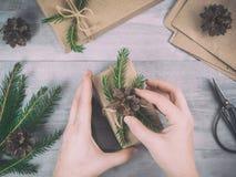 Hände geben eingewickeltes Weihnachtsfeiertagsgeschenk Stockbild