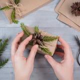 Hände geben eingewickeltes Weihnachtsfeiertagsgeschenk Stockfoto