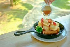 Hände gießen Honig auf Toast und Eiscreme Stockfoto