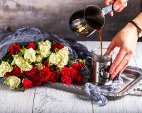 Hände gießt Kaffee in eine Schale Ein Blumenstrauß von Rosen in der Nähe Lizenzfreie Stockfotos