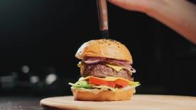 H?nde haften ein Messer in einen Burger Appetitanregender frischer saftiger gekochter Burger Sehr k?stliches Luftbr?tchen und gem stock footage