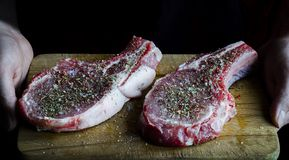 Hände halten ein Brett, auf dem zwei rohe mit Gewürzen besprühte und kochfertige Schweinefleischsteaks sind stockfoto