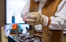 Hände halten ein kleines Metallpferd, gegossen aus geschmolzenem silbernem und geschnitzt stockfotos