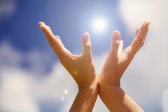 Hände halten hell auf dem blauen Himmel Lizenzfreie Stockfotos