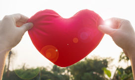 Hände halten oder heben großes rotes Herz zum Himmel mit Blendenfleck und Sonne an Lizenzfreies Stockfoto