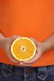 Hände halten Orange an Lizenzfreies Stockfoto