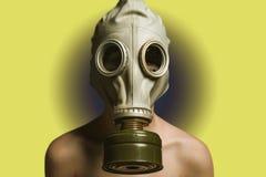Hände hinter seinem zurück, Mann in der Gasmaske auf einem gelben Hintergrund, nackter Torso Lizenzfreie Stockfotos