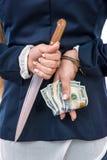 Hände hinter versteckendem Messer und Dollar der Rückseite lizenzfreies stockbild