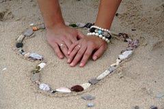 Hände im Herzen im Sand Stockbild