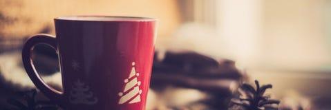 Hände im Rot strickten die Handschuhe, die einen heißen Tasse Kaffee gegen gelben Blatthintergrund halten Konzept von Herbst Zeit stockfoto