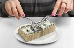 Hände kürzten Geld auf Platte, schnitten Budgetkonzept Lizenzfreies Stockbild