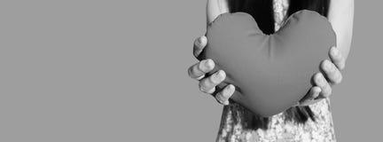 Hände leicht heben an und halten rotes Herz, Liebe und Sorgfalt Lizenzfreie Stockbilder
