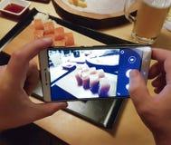 Hände machen Fotos von den blogging Sushi Stockbilder