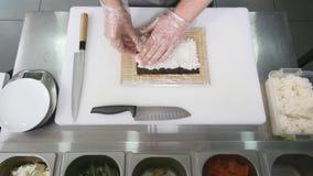Hände machen lange Sushirolle Sushichef, der Fähigkeit demonstriert Berühmter japanischer Teller Beschneidungspfad eingeschlossen Stockbilder
