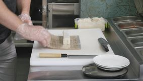 Hände machen lange Sushirolle Sushichef, der Fähigkeit demonstriert Berühmter japanischer Teller Beschneidungspfad eingeschlossen Lizenzfreies Stockfoto