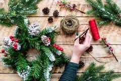 Hände machen Weihnachtskranz Fichtenzweige, Kegel, Threads, Schnur, sciccors auf Draufsicht des hellen hölzernen Hintergrundes Stockfotos