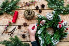 Hände machen Weihnachtskranz Fichtenzweige, Kegel, Threads, Schnur, sciccors auf Draufsicht des hellen hölzernen Hintergrundes Lizenzfreies Stockfoto