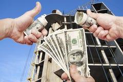 Hände mit Anmerkungsdollar gegen das Haus im Bau Lizenzfreie Stockfotos