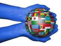 Hände mit Ball mit Flaggen, Karte der Welt gezeichnet Lizenzfreie Stockfotos