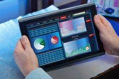 Hände mit Berührungsfläche, während eine Marktstudie überprüft Lizenzfreie Stockfotografie