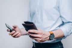 Hände mit brauner Geldbörse und Smartphone stockbilder