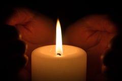 Hände mit brennender Kerze Stockbilder