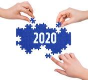 Hände mit dem Puzzlespiel, das Wort 2020 macht Lizenzfreies Stockfoto