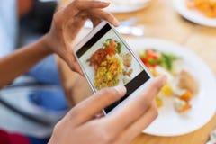 Hände mit dem Smartphone, der Lebensmittel am Restaurant darstellt stockbild