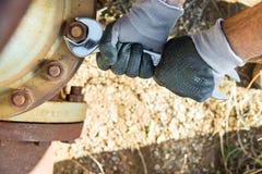 Hände mit den Arbeits-Handschuhen, die einen Schlüssel halten und ziehen sehr Rusty Bolts fest Lizenzfreie Stockbilder