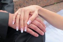 Hände mit den Hochzeitsringen Stockfotos