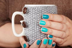Hände mit den manikürten Nägeln, die eine Teeschale mit gestrickter Abdeckung halten Lizenzfreies Stockfoto