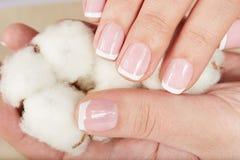 Hände mit der französischen Maniküre, die eine Baumwolle hält, blühen Lizenzfreie Stockfotografie