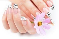 Hände mit der gestreiften Maniküre, die mit Blumen sich entspannt lizenzfreie stockbilder