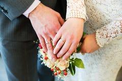 Hände mit Eheringen auf Brautblumenstrauß Lizenzfreie Stockfotografie